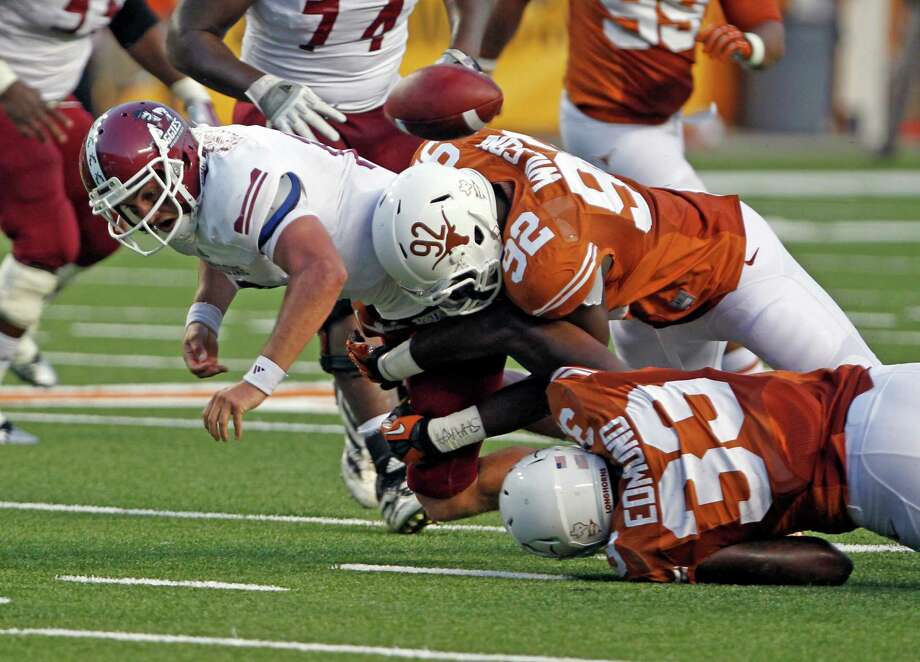 New Mexico State quarterback Andrew McDonald, left, receives fumble-causing hits from Reggie Wilson (92) and  Steve Edmonds (33). Photo: Michael Thomas, FRE / FR65778 AP
