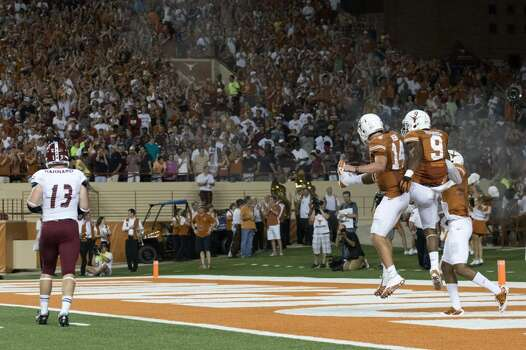 John Harris  of the Longhorns celebrates with quarterback David Ash after catching a 54-yard touchdown pass against the New Mexico State Aggies. Photo: Cooper Neill, Getty Images