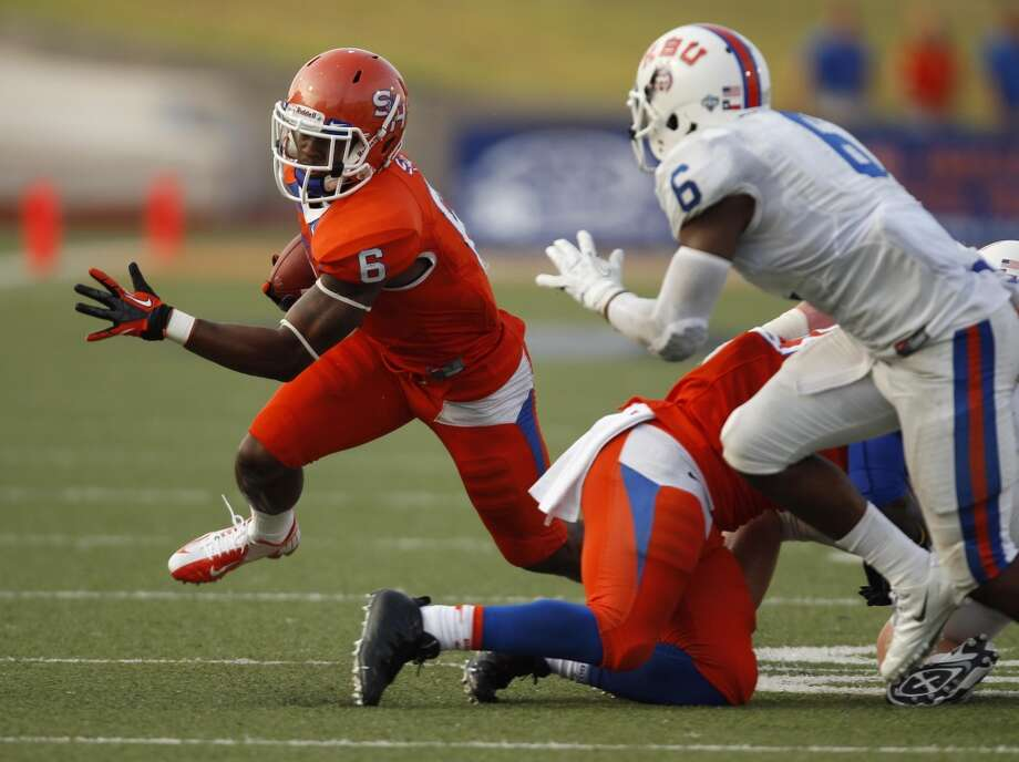 Sam Houston State's Richard Sincere, left, looks for running room as Houston Baptist's Ja'Halen Norris (6) closes in during the first half of a college football game, Saturday, August 31, 2013 at Bowers Stadium in Huntsville, TX. Photo: Eric Christian Smith, For The Chronicle