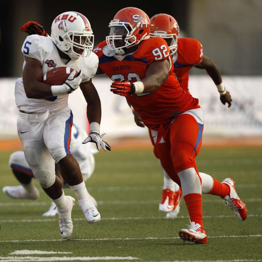 Houston Baptist's B.J. Kelly (5) tries to escape the grasp of Sam Houston State's Chris Pitre (92) during the first half of a college football game, Saturday, August 31, 2013 at Bowers Stadium in Huntsville, TX. Photo: Eric Christian Smith, For The Chronicle