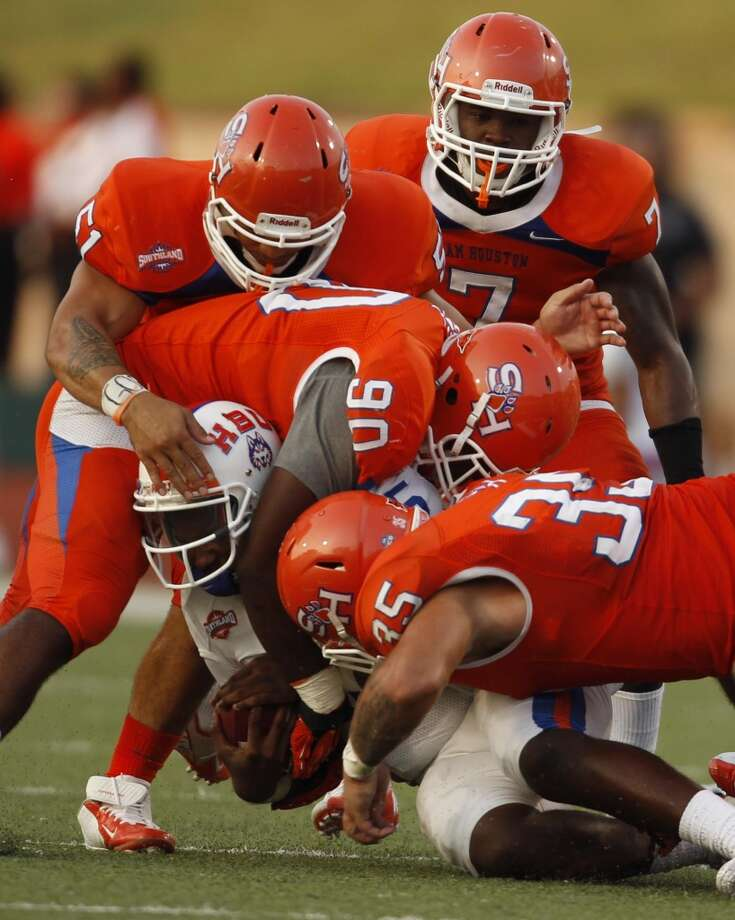 Houston Baptist quarterback Kadarius Baker is smothered by a wall of Sam Houston State defenders during the first half of a college football game, Saturday, August 31, 2013 at Bowers Stadium in Huntsville, TX. Photo: Eric Christian Smith, For The Chronicle