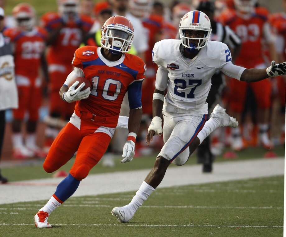 Sam Houston State's Torrance Williams, left, runs past Houston Baptist's John Wesby during the first half of a college football game, Saturday, August 31, 2013 at Bowers Stadium in Huntsville, TX. Photo: Eric Christian Smith, For The Chronicle