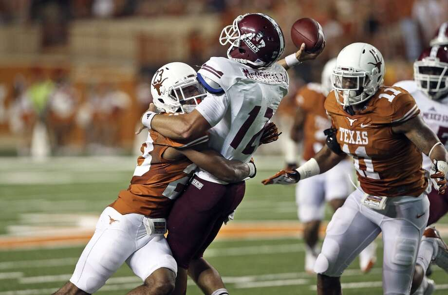 UT defender Carrington Byndom slams into Aggie quarterback Andrew McDonald, breaking up his pass attempt as Texas hosts New Mexico State at Darrell K. Royal - Texas Memorial Stadium on August 31, 2013.