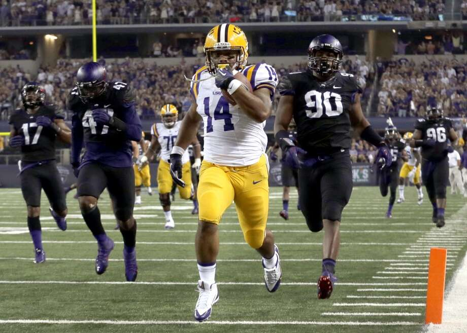 LSU running back Terrence Magee (14) scores a touchdown against TCU's Terrell Lathan (90), Paul Dawson (47) and Sam Carter (17) during the second half of an NCAA college football game, Saturday, Aug. 31, 2013, in Arlington, Texas. (AP Photo/LM Otero) Photo: Associated Press