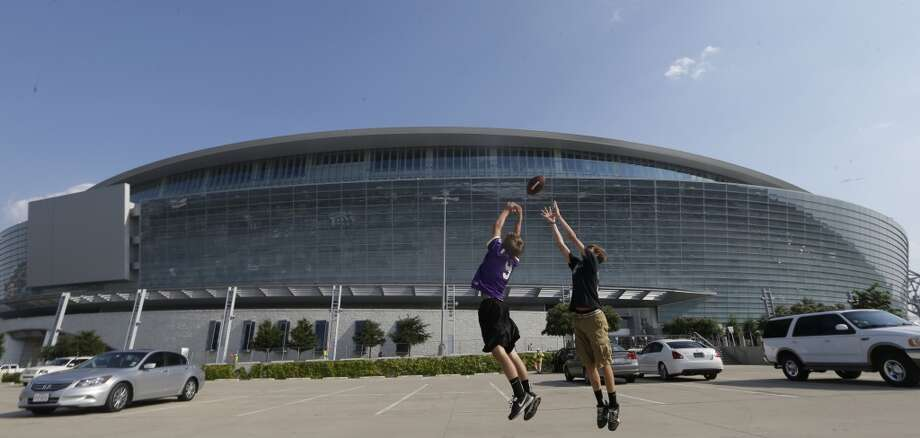 Clinton King, 15, left, and Blayne Enlor, 14, both of Gonzalez, La., jump for a pass as they play catch with friends in the parking lot of AT&T Stadium before the NCAA college football game between LSU and TCU, Saturday, Aug. 31, 2013, in Arlington, Texas. (AP Photo/LM Otero) Photo: Associated Press