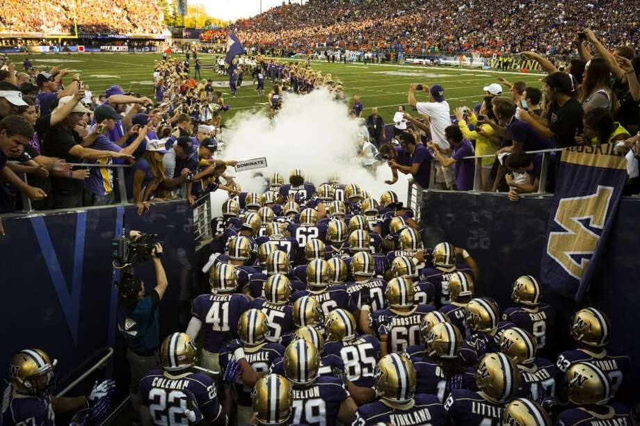 In a swath of smoke and cheering fans, the Washington Huskies pour out onto the turf before the opening season game against Boise State Saturday, August 31, 2013, at the University of Washington's newly-renovated Husky Stadium in Seattle. (Jordan Stead, seattlepi.com) Photo: JORDAN STEAD, SEATTLEPI.COM