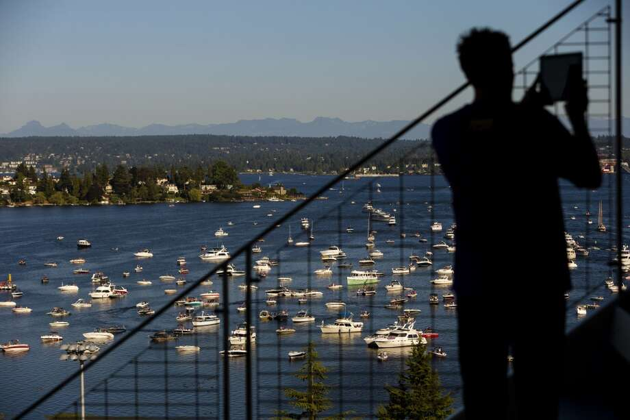 A man photographs a horizon of boats clustered in Lake Washington with a view of University of Washington's newly-renovated Husky Stadium before the opening season game against Boise State Saturday, August 31, 2013, in Seattle. (Jordan Stead, seattlepi.com) Photo: JORDAN STEAD, SEATTLEPI.COM