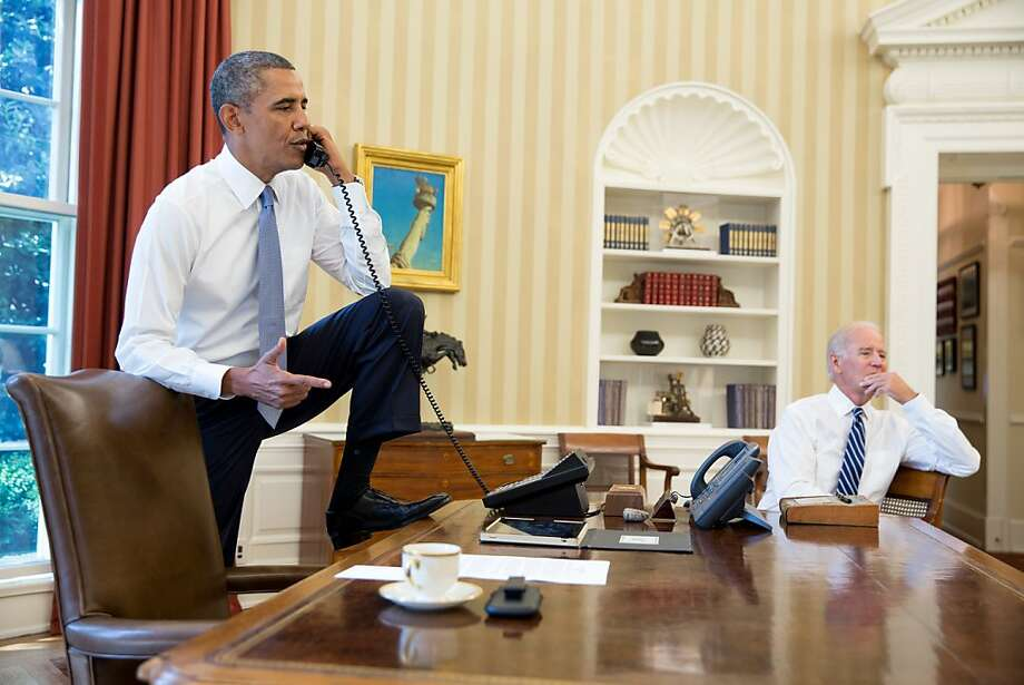 In this handout provided by the White House, U.S. President Barack Obama (L) talks on the phone with Speaker of the House Boehner as Vice President Joe Biden listens  in the Oval Office of the White House August 31, 2013 in Washington, DC. Obama stated that he will seek Congressional authorization for the U.S. to take military action following the alleged Sarin nerve gas used in an attack on Syrian civilians. Photo: Pete Souza, The White House