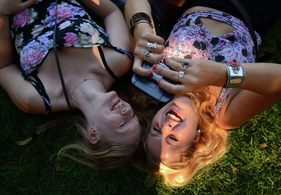 Hannah Unger, left, and Tonada Koch, right, take a break after eating thai food on the first day of the annual Bumbershoot music and arts festival Saturday, Aug. 31, 2013, at the Seattle Center. Photo: SY BEAN, SEATTLEPI.COM / SEATTLEPI.COM