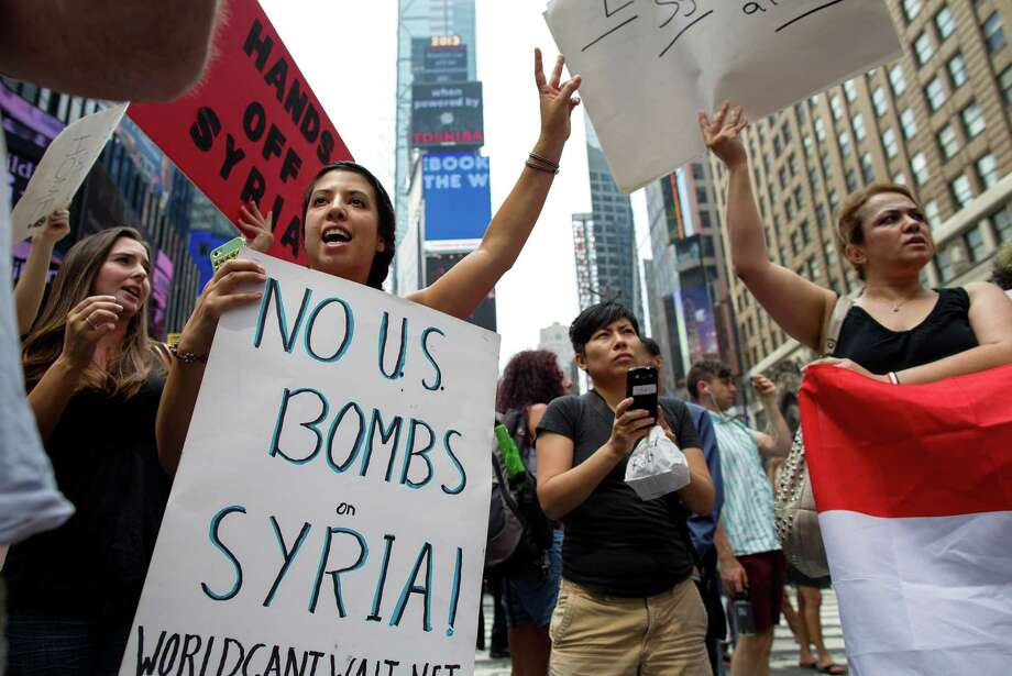 Rachel Lee Richards of New York. left, stands with opponents of a United States military strike against Syria as she and others protest at Times Square in New York Saturday, Aug. 31, 2013. Photo: AP
