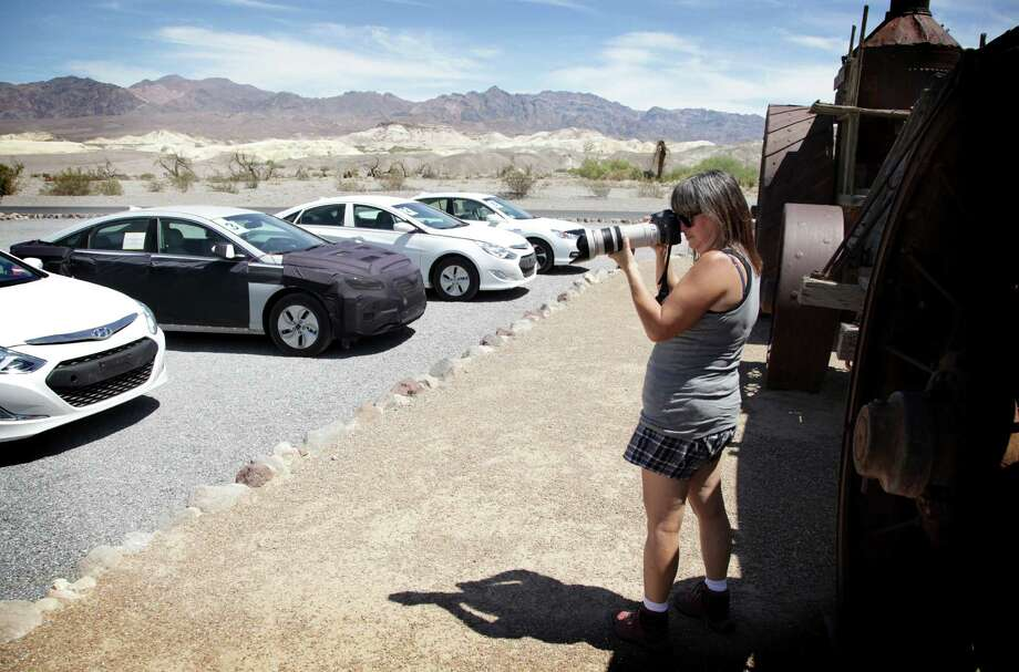 "Brenda Priddy takes a photo of a vehicle in Death Valley National Park in California on Aug.19, 2013. Priddy specializes in ""industrial automotive spy photography.""  She has been working as a photographer full time since the early 1990s, and has photographed thousands of automobiles in development. The world's best known automotive paparraza insists she doesn't chase cars, but she's not above following them. Photo: AP"