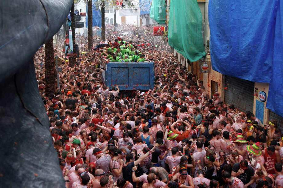 "Crowds of people throw tomatoes at each other during the annual ""tomatina"" tomato fight fiesta in the village of Bunol, 50 kilometers outside Valencia, Spain, Wednesday, Aug. 28, 2013. Thousands of people are splattering each other with tons of tomatoes in the annual ""Tomatina"" battle in recession-hit Spain, with the debt-burdened town charging participants entry fees this year for the first time. Bunol town says some 20,000 people are taking part in Wednesday's hour-long street bash, inspired by a food fight among kids back in 1945. Participants were this year charged some euro10  ($13) to foot the cost of the festival. Residents do not pay. Photo: AP"