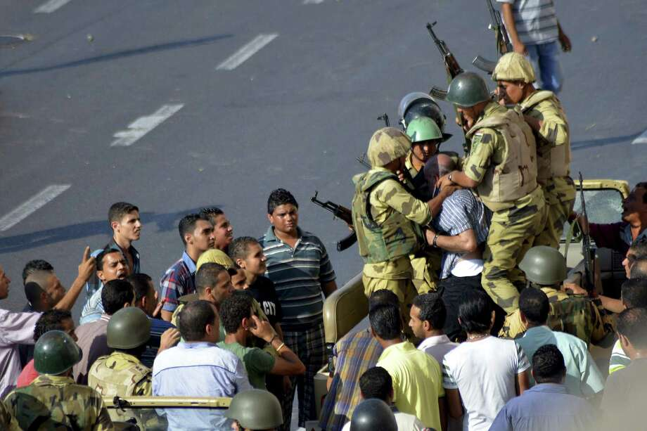 Egyptian soldiers detain a man during clashes between supporters and opponents of Egypt's ousted President Mohammed Morsi in Alexandria, Egypt, Friday, Aug. 30, 2013. Tens of thousands of protesters and Muslim Brotherhood supporters rallied Friday throughout Egypt against a military coup and a bloody security crackdown, though tanks and armored police vehicles barred them from converging in major squares. Photo: AP