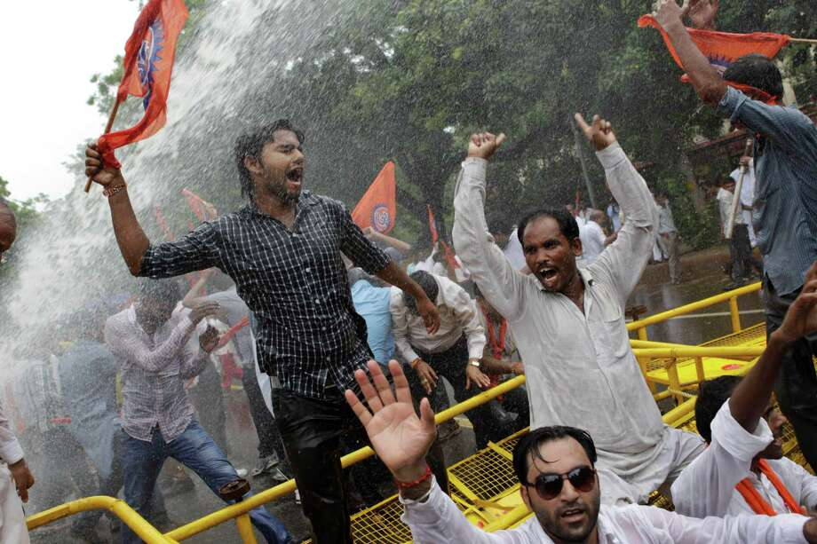 Activists of World Hindu Council or Vishwa Hindu Parishad (VHP) shout as they are hit with a police water cannon during a protest in New Delhi, India, Monday, Aug. 26, 2013. Hundreds of Hindu nationalists have clashed with police outside India's Parliament after being barred from conducting a religious march at a disputed holy site in the city of Ayodhya, 550 kilometers (350 miles) east of New Delhi, at the heart of deadly clashes between Hindus and Muslims. Photo: AP