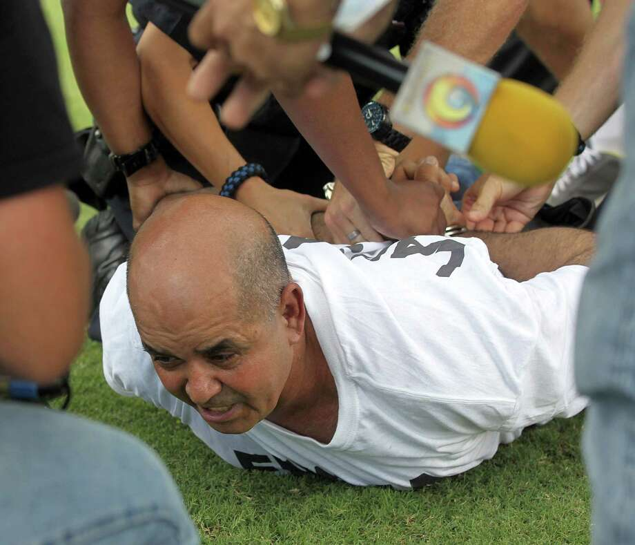 Fort Lauderdale police officers handcuff Cuban exile Diego Tintorero after he jumped to the field holding a sign and ran to the dugout of Cuban baseball team Industriales during a baseball game against former team players now living in exile, Saturday, Aug. 31, 2013, in Fort Lauderdale, Fla. (AP Photo/El Nuevo Herald, Pedro Portal)  Photo: AP