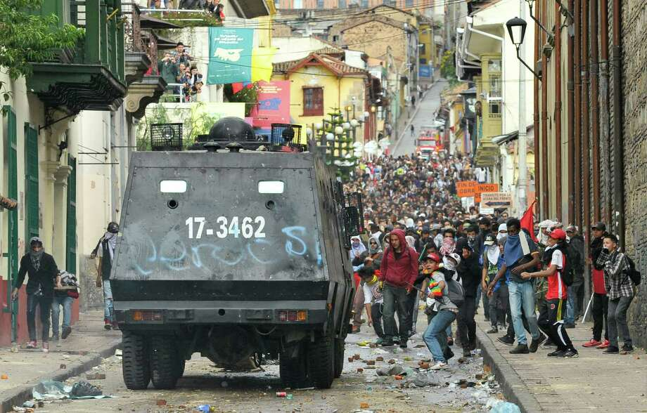 Students throw stones at a police vehicle during protests in Bogota, Colombia, Thursday, Aug. 29, 2013. Students protested in support of farmers who have being blockading Colombian highways for more than 10 days for an assortment of demands that include reduced gasoline prices, increased subsidies and the cancellation of free trade agreements. Photo: AP