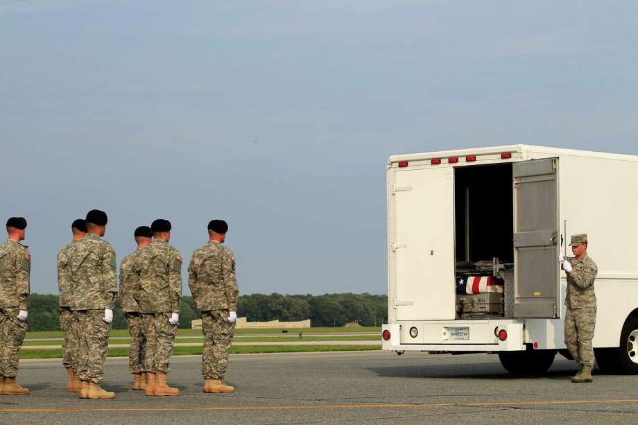 Airman Christopher Cox prepares to close the door of the transfer vehicle carrying the remains of Army Sgt. 1st Class Ricardo D. Young of  Rosston, Ark., and Army Staff Sgt. Michael H. Ollis of Staten Island, N.Y., after their arrival at Dover Air Force Base, Del. on Saturday, Aug. 31, 2013. The Department of Defense said Young and Ollis were supporting Operation Enduring Freedom in Afghanistan. Photo: AP