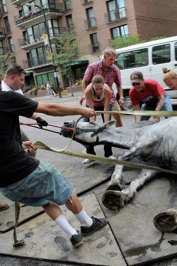 In this Aug. 17, 2013, file photo,  provided by People for the Ethical Treatment of Animals, (PETA) shows people helping Jerry, a carriage horse, stand up after he collapsed pulling a carriage on the streets of Salt Lake City, Utah. A Utah business owner who drew criticism after his carriage horse collapsed in downtown Salt Lake City says the animal has died. Carriage for Hire owner Blaine Overson tells KSL-TV the horse named Jerry died Friday, six days after he collapsed near Temple Square on Aug. 17. Photo: AP