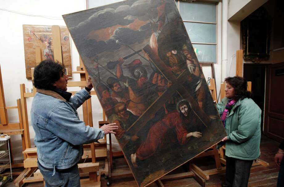 "In this Aug. 21, 2013 file photo, workers from the Culture Ministry display a recovered 18th century painting by an anonymous artist depicting Jesus in La Paz, Bolivia. This painting titled ""Jesus con la Cruz a Cuesta"" was stolen from the San Pedro de la Paz church in Bolivia on June 11, 2003, and recovered in the Peruvian capital of Lima in April 2005.  Increasingly bold thefts plague colonial churches in remote Andean towns in Bolivia and Peru, where religious and civil authorities say cultural treasures are disappearing at an alarming rate. Photo: AP"