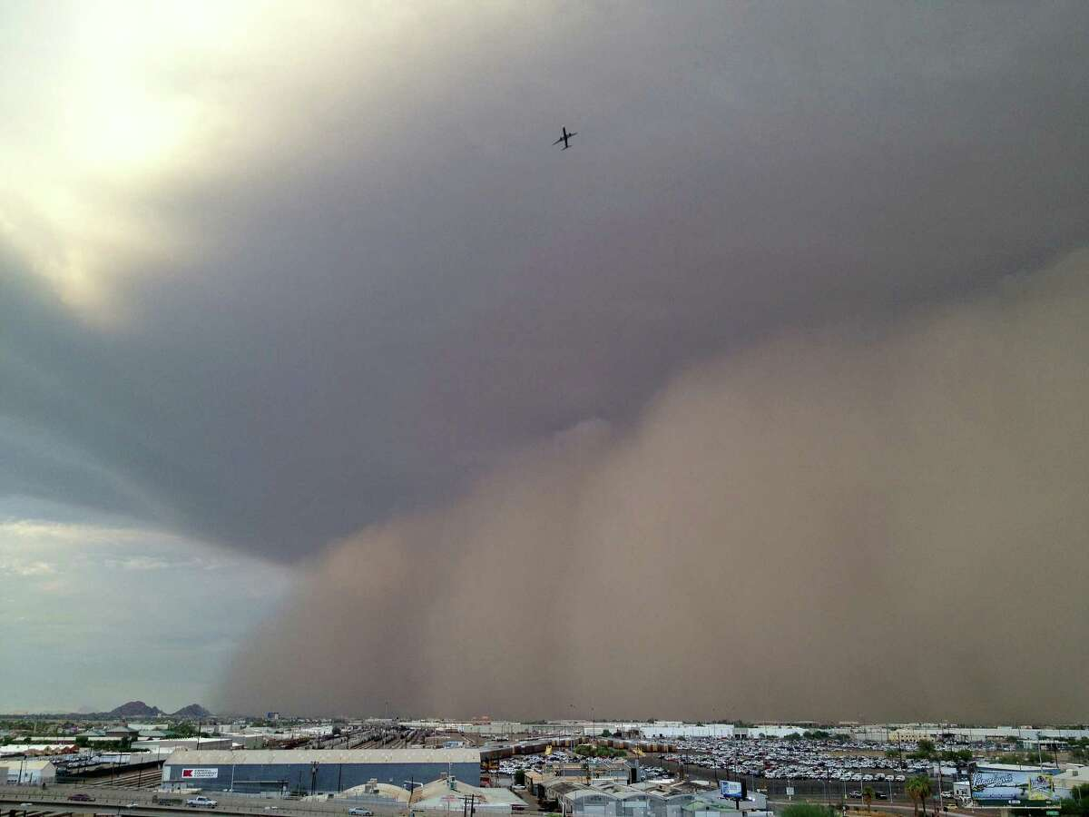 A jetliner soars safely ahead of a massive wall of dust hundreds of feet high as a large dust storm moves across downtown Phoenix early Monday, Aug. 26, 2013. Flights out of Phoenix Sky Harbor International Airport were suspended while the storm passed through the area.