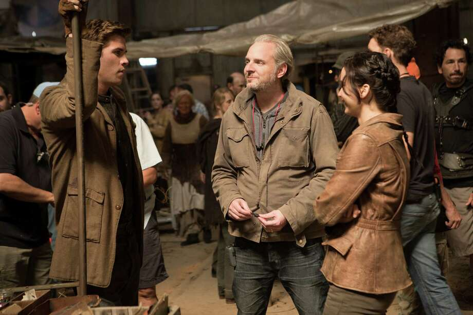 "This film image released by Lionsgate shows director Francis Lawrence, center, on the set with actors Liam Hemsworth, left, and Jennifer Lawrence during the filming of ""The Hunger Games: Catching Fire."" Photo: AP"