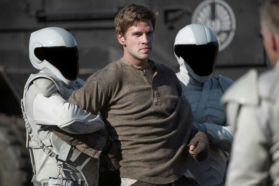 "This film image released by Lionsgate shows Liam Hemsworth, center, in a scene from ""The Hunger Games: Catching Fire."" Photo: AP"