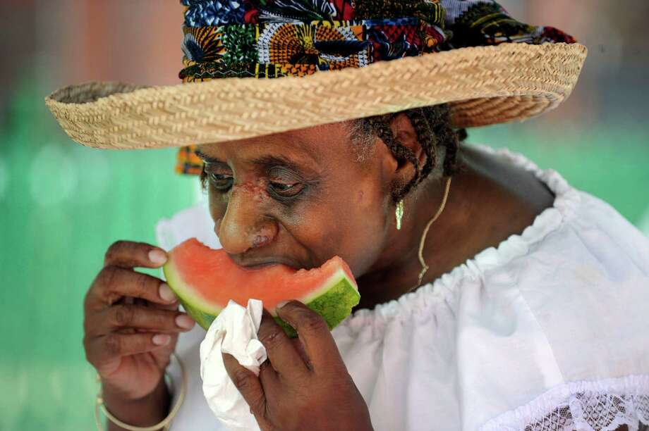 Adrienne Ashley of Bridgeport enjoys a piece of watermelon at the Caribbean Jerk Festival  held on the CityCenter Green in Danbury, Conn., Sunday, Sept. 1, 2013. Photo: Carol Kaliff / The News-Times