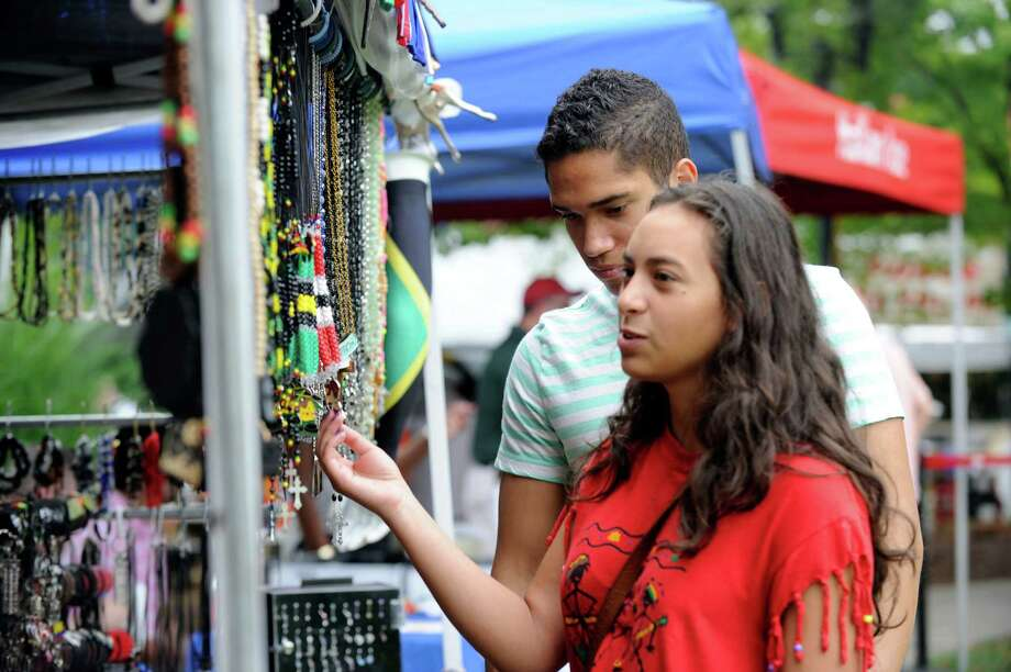 Havier Perez, 17, of Waterbury, Conn. and Keren Carrion, 15, of Danbury, look at items for sale at the  Caribbean Jerk Festival, held on the CityCenter Green in Danbury, Conn., Sunday, Sept. 1, 2013. Photo: Carol Kaliff / The News-Times