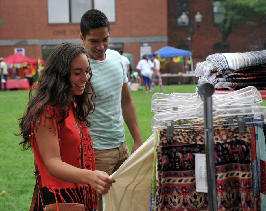 Keren Carrion, 15, of Danbury, and Havier Perez, 17, of Waterbury look at items for sale at the  Caribbean Jerk Festival, held on the CityCenter Green in Danbury, Conn., Sunday, Sept. 1, 2013. Photo: Carol Kaliff / The News-Times