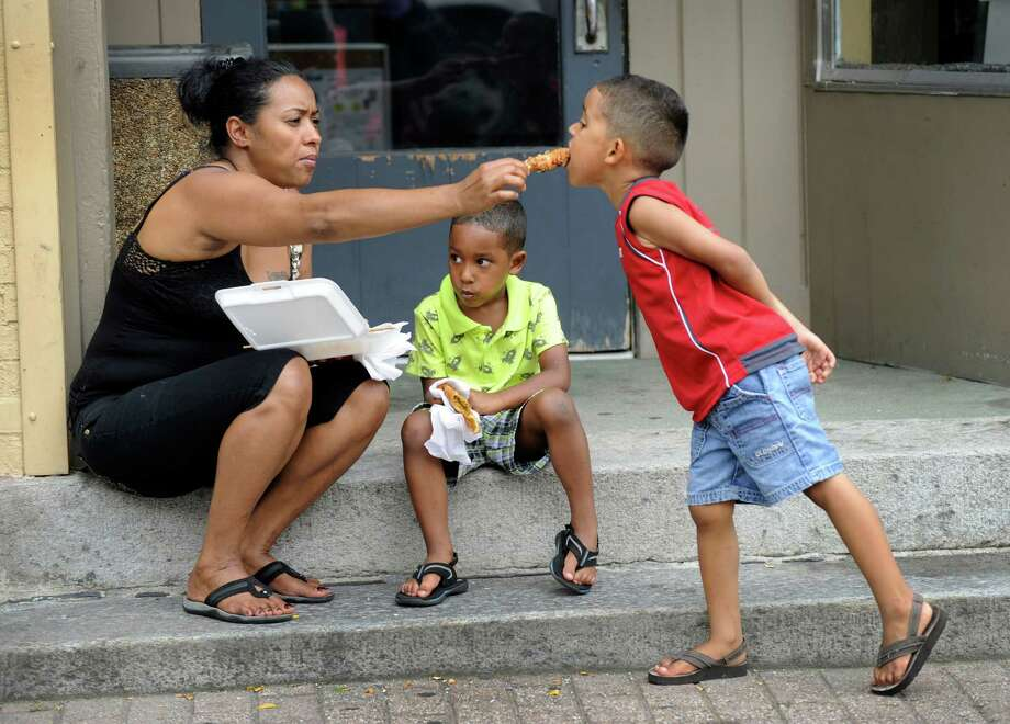 Luisa Gutierrez of Danbury, originally from the Dominican Republic, shares her lunch with twin sons, Kenny, right, and Kendrick Hernandez, age 4 1/2, a tthe Caribbean Jerk Festival held on the CityCenter Green in Danbury, Conn., Sunday, Sept. 1, 2013. Photo: Carol Kaliff / The News-Times