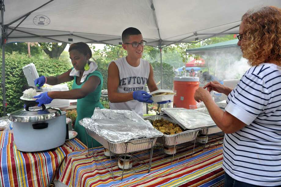 Yvonne Cook, left, of Danbury and Shawn Silva of Bethel serve Guyanese chicken curry at their booth at the Caribbean Jerk Festival is held on the CityCenter Green in Danbury, Conn., Sunday, Sept. 1, 2013. Photo: Carol Kaliff / The News-Times