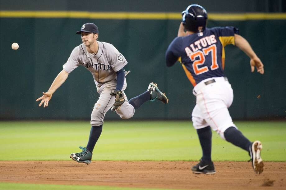 Mariners second baseman Nick Franklin flips to shortstop Brad Miller to force Houston Astros second baseman Jose Altuve at second base for the final out of the fifth inning. Photo: Smiley N. Pool, Houston Chronicle