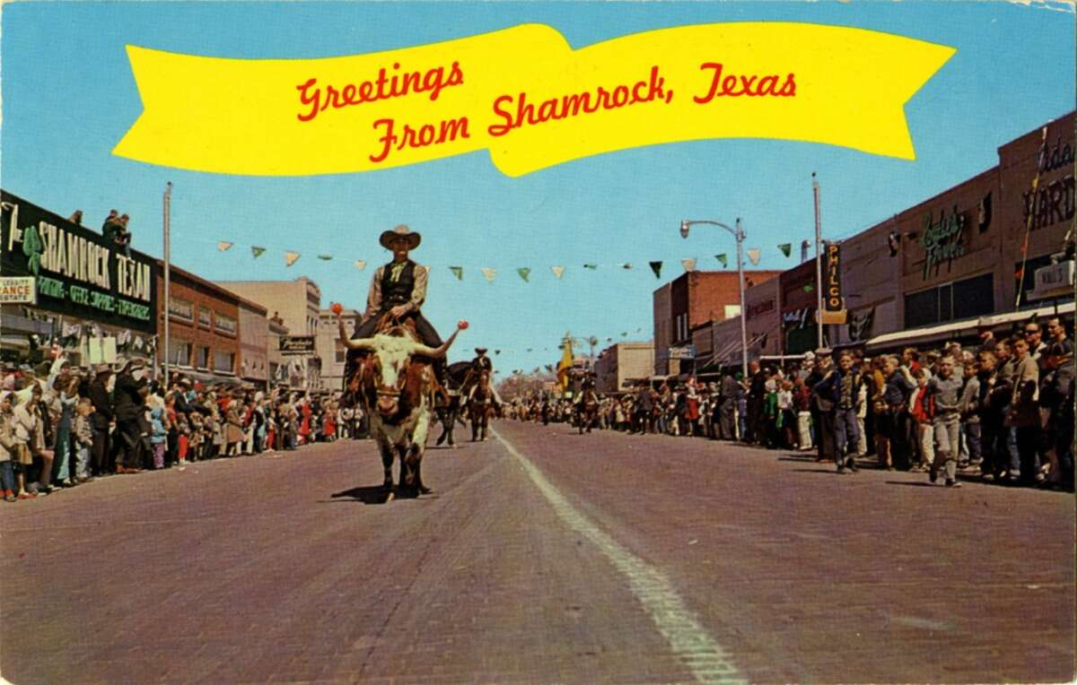 UNITED STATES - CIRCA 1900: Postcard view of the famous St. Patrick's Day Parade showing people lining the main street as cowboys ride steers in the parade. (Photo by Lake County Museum/Getty Images)