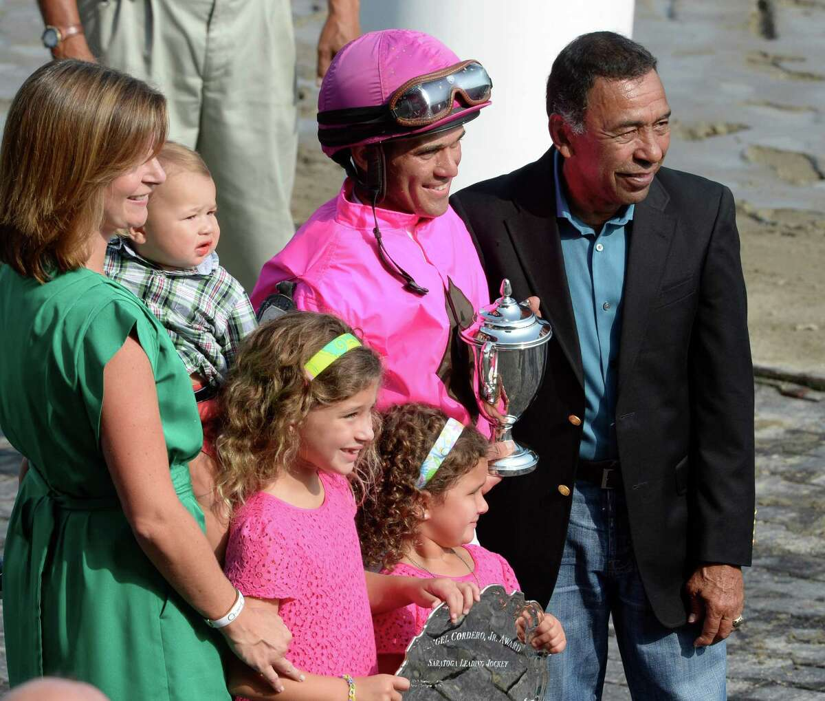 Jockey Javier Castellano, center stands in the winner's circle as he receives Top Jockey of Meeting award Sept. 1, 2013, at the Saratoga Race Course in Saratoga Springs, N.Y. With Castellano is his wife Abbey and his children and Angel Corder Jr. for which the award is named. (Skip Dickstein/Times Union)