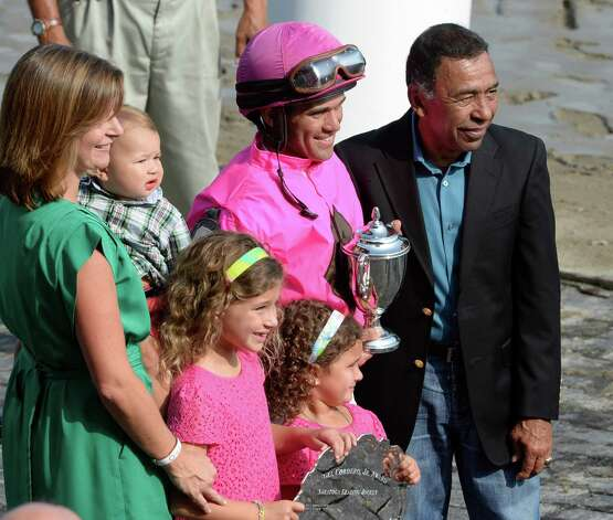 Jockey Javier Castellano, center stands in the winner's circle as he receives Top Jockey of Meeting award Sept. 1, 2013,  at the Saratoga Race Course in Saratoga Springs, N.Y. With Castellano is his wife Abbey and his children and Angel Corder Jr. for which the award is named.   (Skip Dickstein/Times Union) Photo: SKIP DICKSTEIN