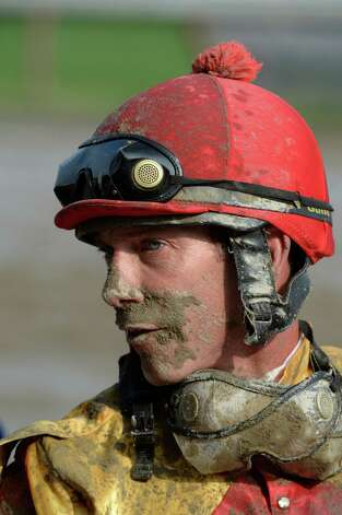 Jockey Mike Luzzi shows the muddy condition of the race track Sept. 1, 2013,  at the Saratoga Race Course in Saratoga Springs, N.Y.     (Skip Dickstein/Times Union) Photo: SKIP DICKSTEIN