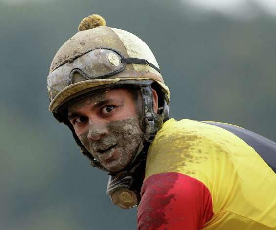 Jockey Shaun Bridgmohan shows the muddy condition of the race track Sept. 1, 2013,  at the Saratoga Race Course in Saratoga Springs, N.Y.     (Skip Dickstein/Times Union) Photo: SKIP DICKSTEIN