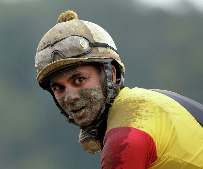 Jockey Shaun Bridgmohan shows the muddy condition of the race track Sept. 1, 2013,  at the Saratoga