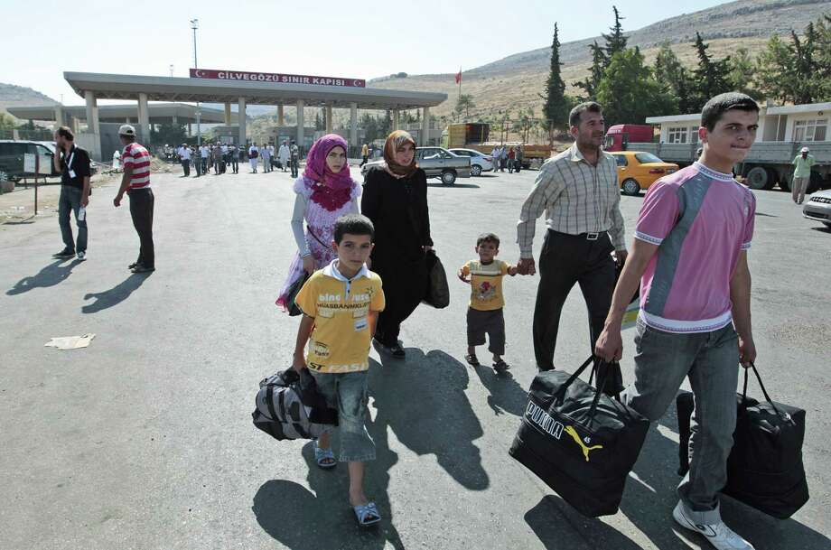 Syrian refugees pass through the Turkish Cilvegozu gate border crossing amid the crisis of alleged chemical warfare in Syria and the possibility of foreign intervention, particularly from the U.S. Photo: Gregorio Borgia / Associated Press