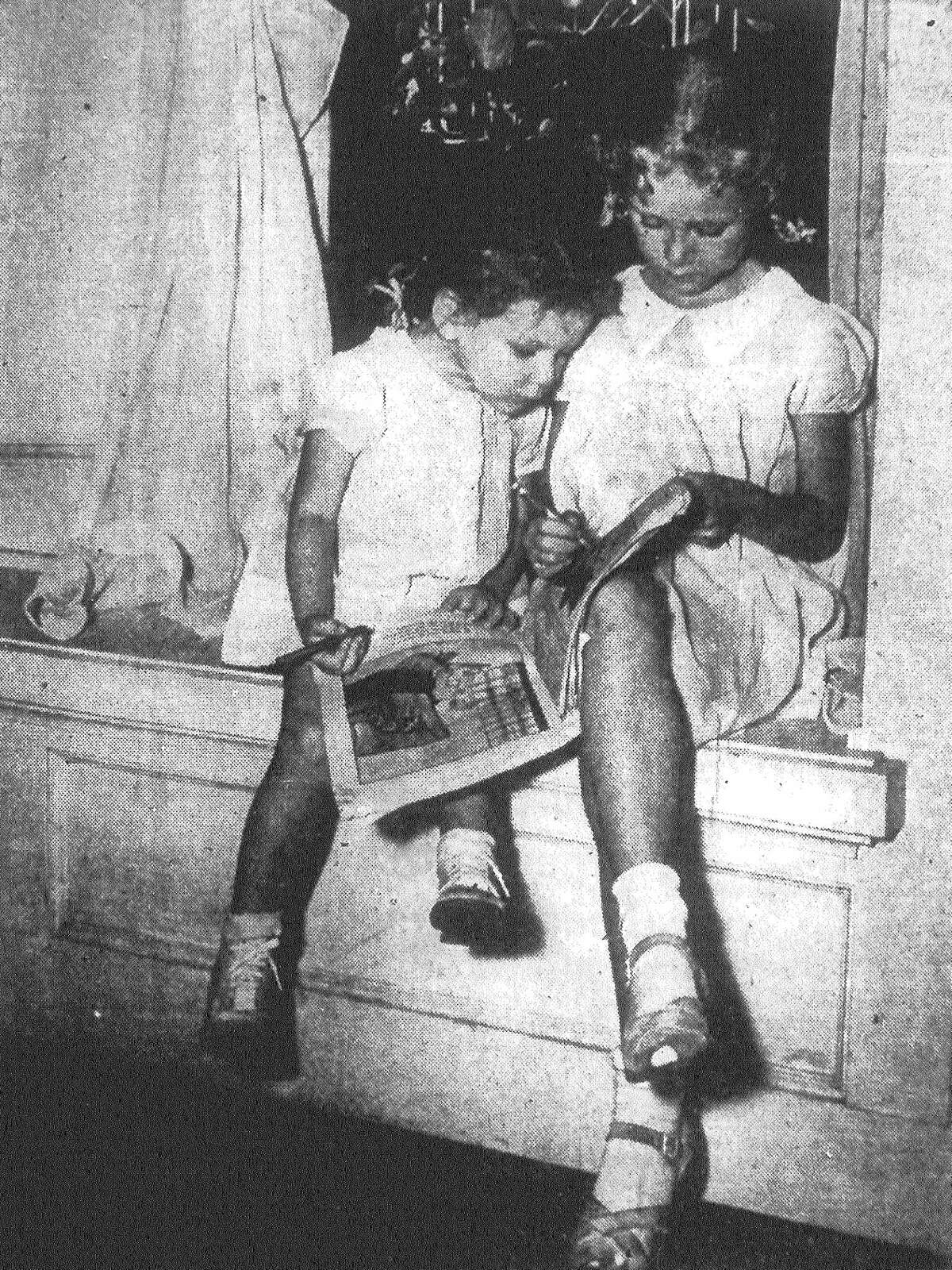 Judy Jones, who lives in the 300 block of Joliet St., explains to her little sister, Scharlie, just how coloring and other activities are staged at the school where Judy will start in the next day or two. The children's father is missing on Bataan. Published in the San Antonio Express Sept. 5, 1943.
