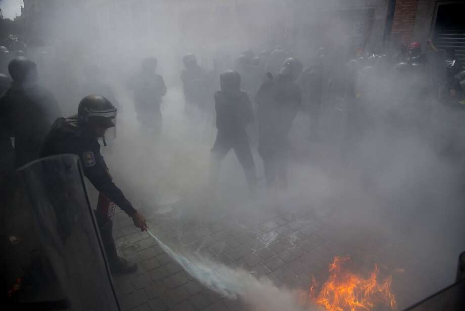 Riot police try to put out a fire during clashes with a group of anarchists in Mexico City, Sunday, Sept. 1, 2013. Teachers, anarchists and other groups protesting against the proposed energy and education reforms are marching separately towards the national congress as Mexican president Enrique Pena Nieto sends his Interior Minister to congress to deliver the written version of his first State of the Nation and a day later, Pena Nieto will offer his State of the Nation address. (AP Photo/Eduardo Verdugo) Photo: Eduardo Verdugo, Associated Press