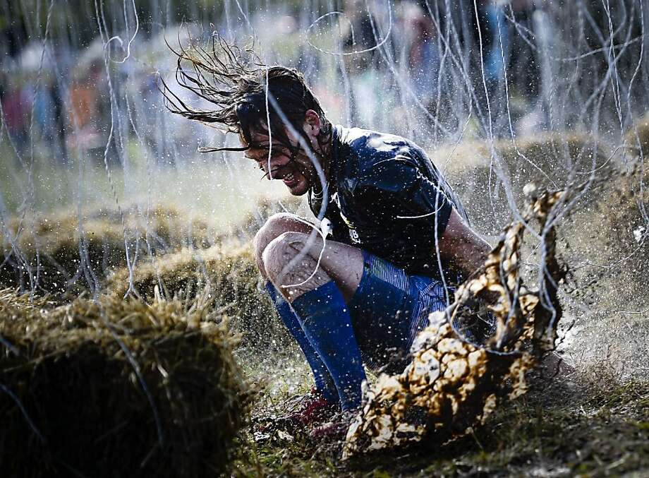 Shock absorber: A racer splashes a mud puddle while trying to evade 10,000-volt wires (low amperage presumably ) during the Tough 