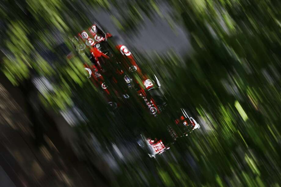 Scott Dixon, of New Zealand, drives under a canopy of leaves during the IndyCar Grand Prix of Baltimore auto race on Sunday, Sept. 1, 2013, in Baltimore. (AP Photo/Patrick Semansky) Photo: Patrick Semansky, Associated Press
