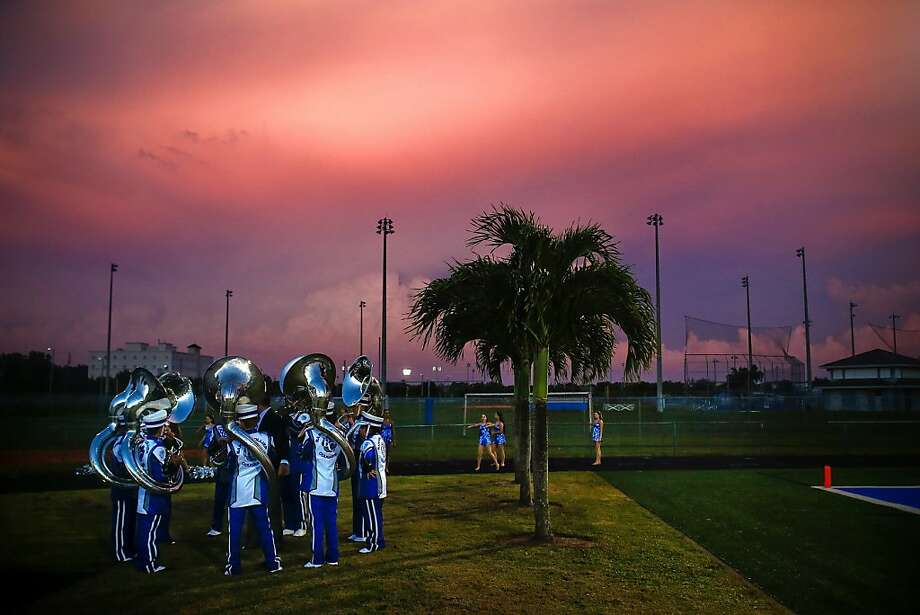 Well, the trumpets, trombones and French horns are AWOL, so I guess it's up to us: The Barron Collier High School brass section warms up before halftime of the Barron Collier-Miami Braddock game in Naples, Fla. Photo: Scott McIntyre, Associated Press