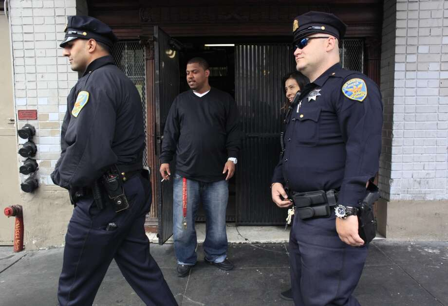 Jessie Deming, general manager of the Henry Hotel on 6th Street, watches as a team of San Francisco Police Officers walk past his hotel. Photo: Mike Kepka, The Chronicle