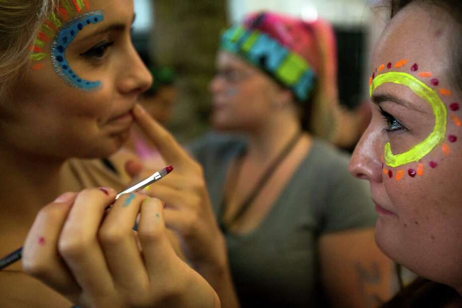Women get their faces painted on the second day of the annual Bumbershoot arts and music festival Sunday, September 1, 2013, at Seattle Center in Seattle. The festival continues Monday. Photo: JORDAN STEAD, SEATTLEPI.COM / SEATTLEPI.COM