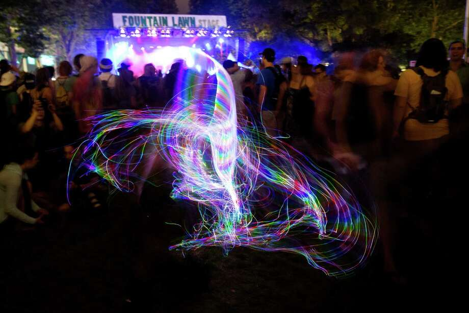 In this long exposure, onlookers spin colorful light ropes during a performance by Beats Antique on the second day of the annual Bumbershoot arts and music festival Sunday, September 1, 2013, at Seattle Center in Seattle. The festival continues Monday. Photo: JORDAN STEAD, SEATTLEPI.COM / SEATTLEPI.COM