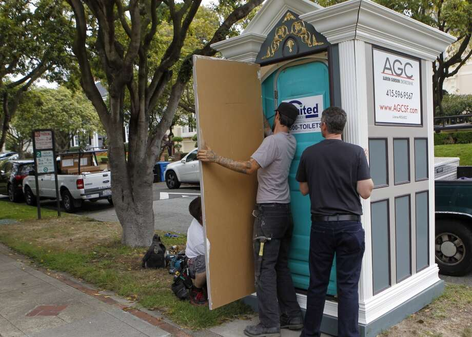 Contractor Aaron Gordon (right) shoves a porta-potty into a booth designed to disguise the toilet at  a residential work site in the St. Francis Wood neighborhood. Photo: Paul Chinn, The Chronicle