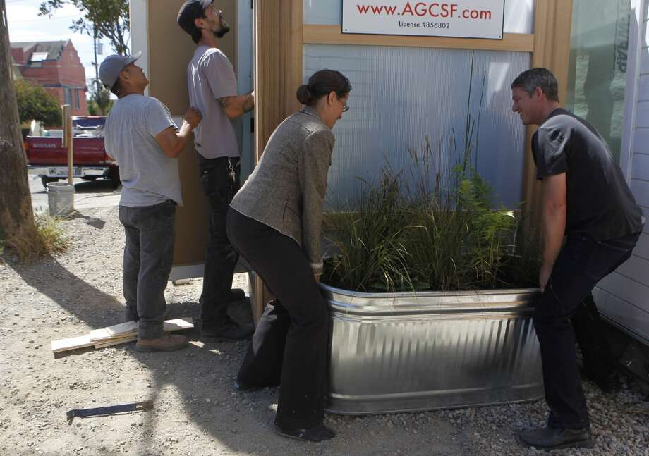 "Contractor Aaron Gordon (right) and architect Karen Curtiss adjust a planter by the ""P-Cycle,"" a portable toilet that recycles urine to irrigate plants. Photo: Paul Chinn, The Chronicle"