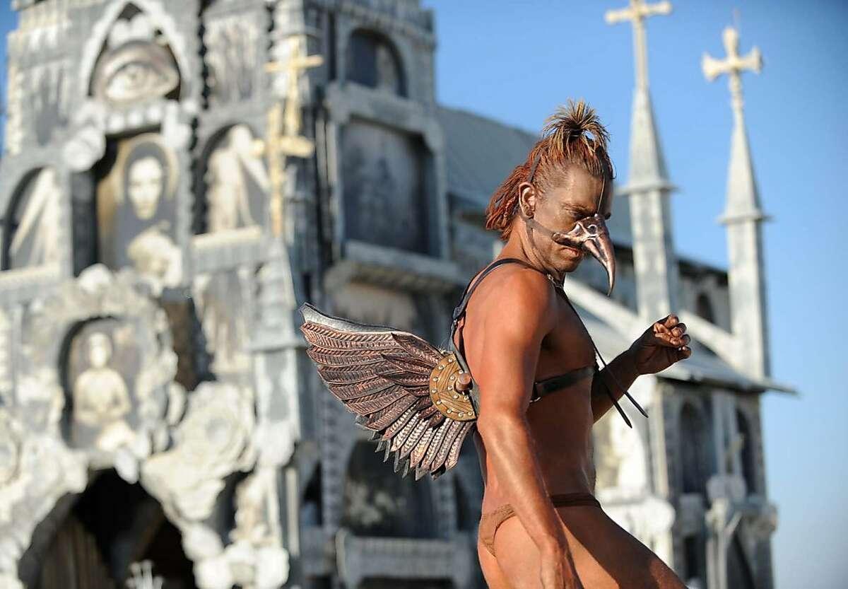 A man in a bird costume walks around in stilts next to the